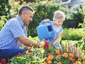 Grandfather and Granddaughter watering Garden together